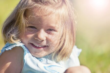 Portrait of joyfully smiling little girl sitting in grass, close up.