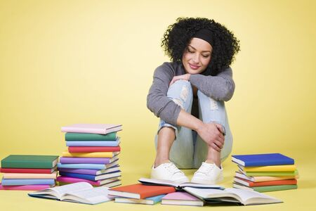 Joyful smiling student girl sitting on the floor and learning surrounded by colorful books, isolated on yellow background.