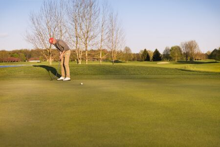 Male golf player putting ball on green in evening time, with empty copyspace.