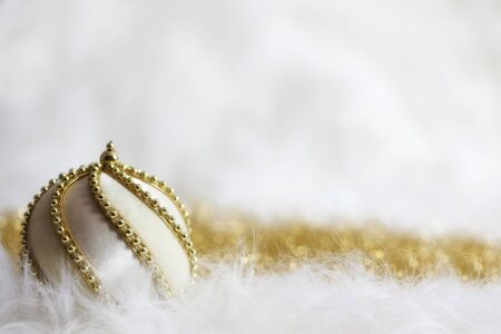 White Christmas bauble adorned with golden chain on twinkling goldenwhite background