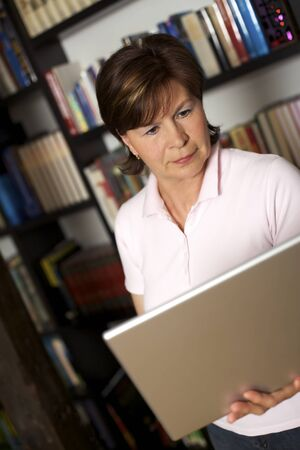 Pretty modern senior woman standing in front of bookshelf and holding a laptop. Stock Photo