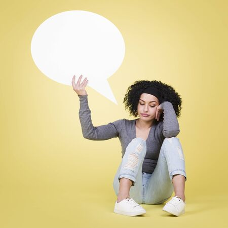 Unhappy woman being sad about being lonely holding a white blank paper speech bubble with copy space for text, isolated on yellow background.