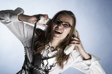 Furious telephonist in call center wrapped with phone cables being overstrained with work, isolated on blue background.