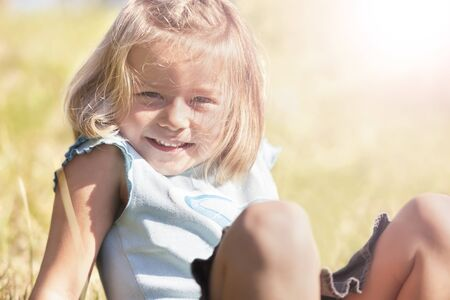 Portrait of joyfully smiling little girl sitting outdoors in grass. Stockfoto