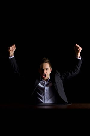 Young modern businessman in dark suit sitting at office desk and raising hands celebrating business success, low-key image isolated on black background.