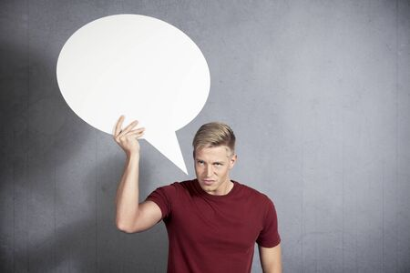 Furious man looking with anger while holding white blank speech bubble with space for text isolated on grey background.