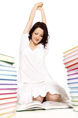 Pretty smiling young woman sitting on floor between two stacks of colorful books reading and stretching herself, isolated on white background.