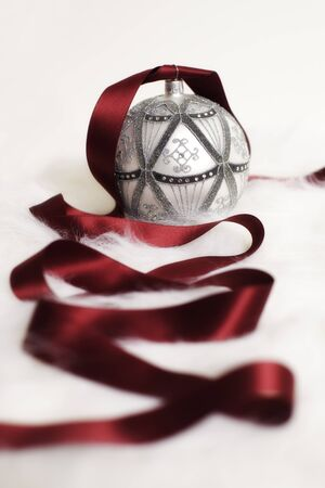 Arrangement of silver Christmas bauble with red ribbon on white fur background