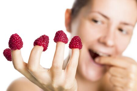 Close up of raspberries on fingers with blurred happy girl enjoying eating raspberry isolated on white background.
