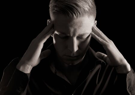 Low-key close up portrait of young serious man in dark shirt with hand at temples and closed eyes, black and white, isolated on black background.