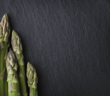 Bunch of asparagus isolated on dark grey slate stone with empty copyspace.