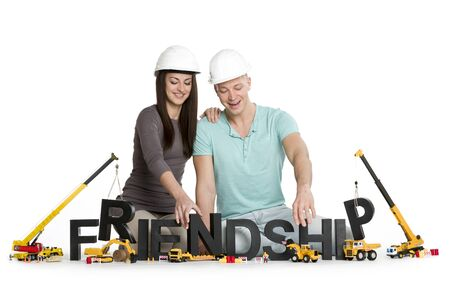 Building up friendship concept: Joyful man and woman developing the word friendship along with construction machines, isolated on white background.