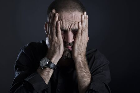 Stressed man looking exhausted, covering face with hands, isolated on black background. Stockfoto