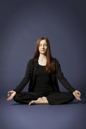Young lady practicing yoga in lotus posture (Padmasana) and fingers in Chin Mudra with eyes closed in black clothes on blue background.