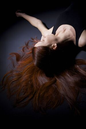 Young woman lying on floor with brunette long hair spread out over dark floor.