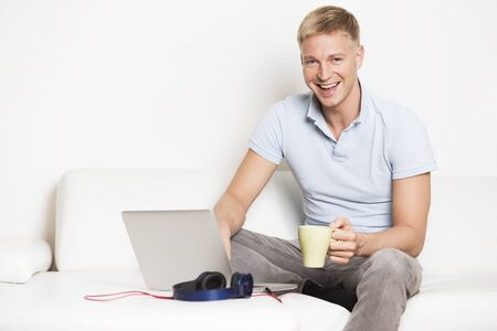 Laughing attractive young man sitting on sofa with laptop, headsets and a cup of coffee in his hand.
