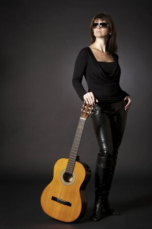 Full-body portrait of glamorous young woman in black posing with guitar on floor, isolated on black background.