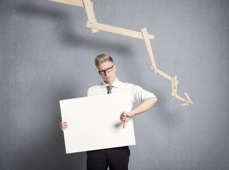 Concepto: declive empresarial. Hombre de negocios disgustado dando pulgares hacia abajo en el letrero vacío blanco con espacio para texto delante del gráfico de negocios con tendencia negativa, aislado sobre fondo gris.