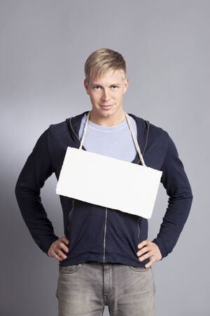 Smiling confident man holding white blank signboard with space for text isolated on grey background.