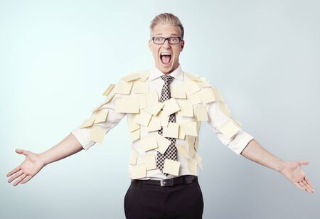 Overburdened shouting businessman covered by many empty yellow stickers with space for text, isolated.