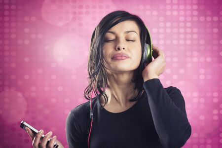 Young joyous girl listening to music with headphones and mp3 player with eyes closed, in calm and relaxed mood, isolated on pink disco background.