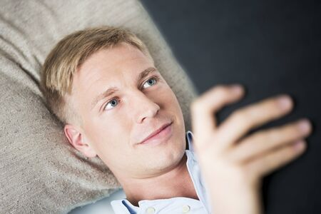 Close up portrait of young smiling man relaxing and reading a book, lying on sofa at home.