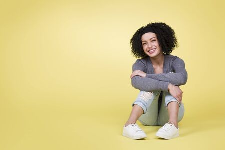 Joyful smiling woman sitting on yellow isolated background with empty copy space. Banco de Imagens