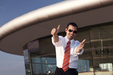 Happy businessman showing both thumbs up, office building in background.