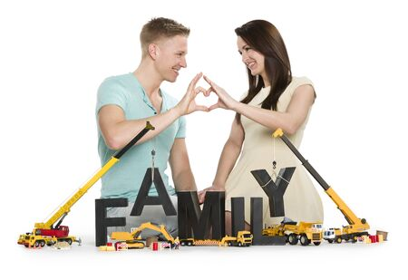 Starting a family concept: Loving young couple holding hands in heart shape along with construction machines building the word family, isolated on white background. Stockfoto