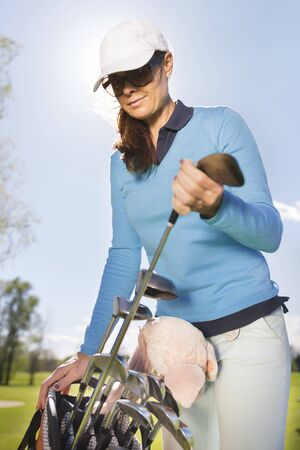 Female golf player taking golf club from bag on a summer day.