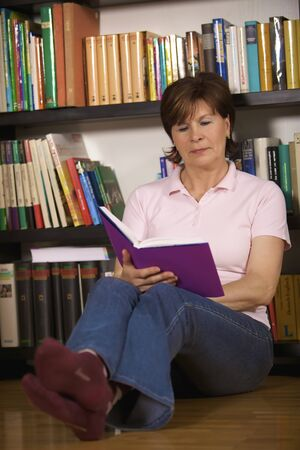 Friendly senior woman sitting on floor in front of bookshelf at home and reading a book. Stock Photo