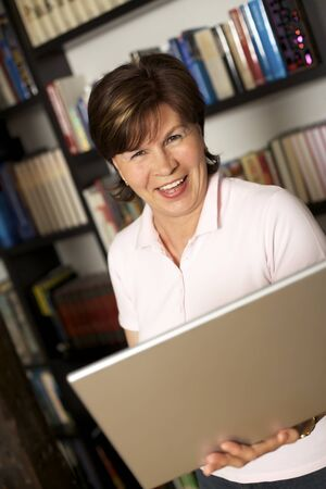 Laughing modern senior woman standing in front of bookshelf and holding a laptop.