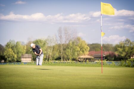 Male senior golf player shooting onto green, with flag in hole in foreground. 写真素材