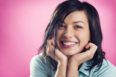 Close up portrait of smiling, happy, girl with hands at chin looking straight, isolated on pink background. Stockfoto