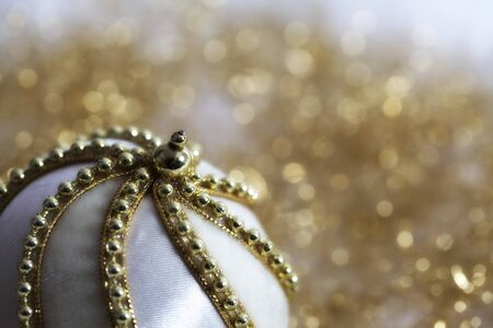 White Christmas bauble adorned with golden chain on twinkling golden background