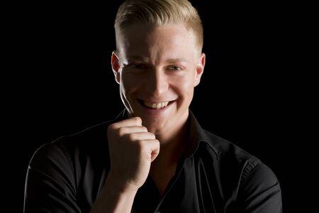 Retrato discreto de guapo feliz en camisa oscura con puño delante de la barbilla mirando recto, aislado sobre fondo negro. Foto de archivo
