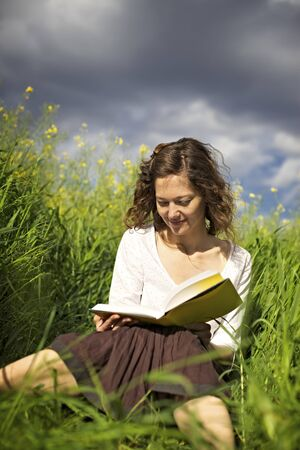 Young smiling woman sitting in green field and reading a book.