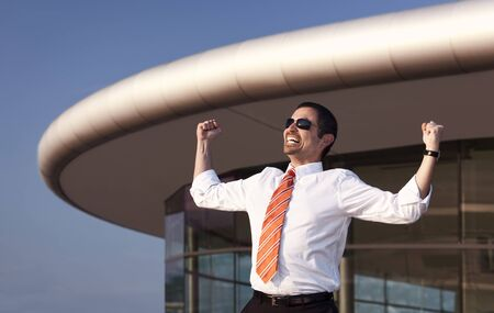 Successful business person in white shirt, orange tie and sunglasses raising his hands in front of office building and blue sky. Stockfoto