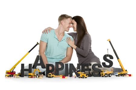 Developing happiness concept: Loving young couple along with construction machines building the word happiness, isolated on white background.