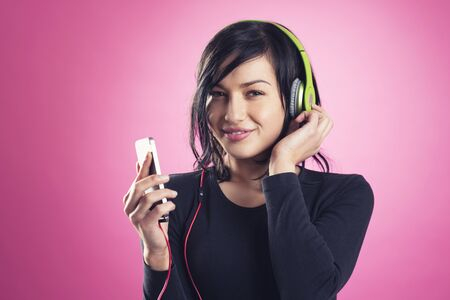 Smiling happy girl enjoying listening to music with headphones and mp3 player, isolated on pink background. Stockfoto