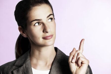Close-up of young businesswoman pointing upwards. Reklamní fotografie