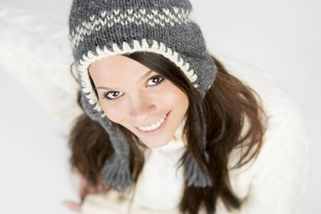 Close up of sweet young girl in winter pullover and cap, looking up with a charming smile on her face, isolated on grey background.