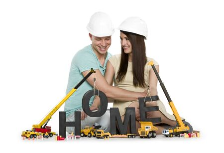 Building up home concept: Happy young man and woman along with construction machines building the word home, isolated on white background. Stockfoto
