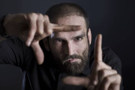 Serious focused man showing frame with fingers, isolated on black background.