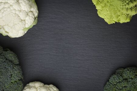 Several cauliflower varieties isolated on a dark stone plate, looking classy.