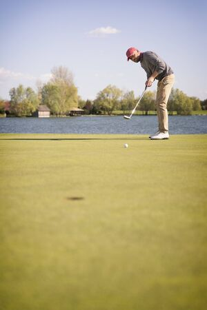 Male golf player putting with golf club on green, with lake in background and blank copyspace.
