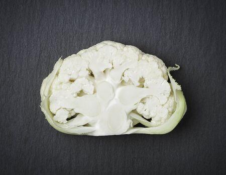 Cut in half white cauliflower vegetable, isolated on dark slate stone slab. Stockfoto