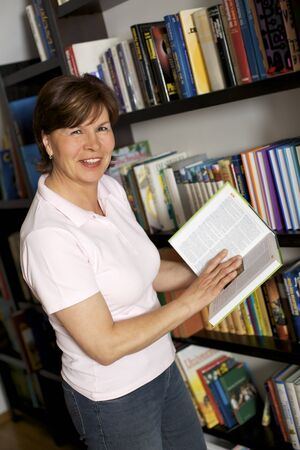Smiling senior woman standing in front of bookshelf at home and carrying books.