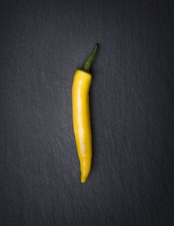 One yellow hot chili pepper looking classy and minimalist, isolated on dark stone slab. 스톡 콘텐츠