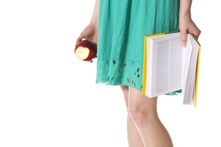 Close up of girl in green dress holding a book and an apple symbolizing: reading or knowledge is good for you, isolated on white background with plenty of copy-space. Stockfoto